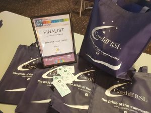 excellence in sustainability finalist award on display with reusable tote bags